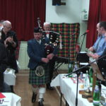 Neil Bremner pipes in the haggis as Bob Robertson carries the beast